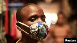 """Eugene Amuri, moteki na nzela na wenze ya Kimironko azipi zolo mpe monoko na """"kitenge"""" masque ya liputa mpo na komibatela na coronavirus ya sika (COVID-19), Kigali, Rwanda, 17 mars 2020. REUTERS/Maggie Andresen"""