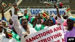 Des manifestants scandent des slogans et agitent le drapeau national du Zimbabwe au cours d'un rassemblement visant à dénoncer les sanctions économiques américaines et européennes, à Harare, le 25 octobre 2019. (AFP)