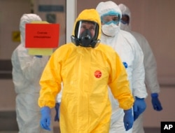Russian President Vladimir Putin, center, wearing a protective suit enters a hall during his visit to the hospital for coronavirus patients in Kommunarka settlement, outside Moscow, March 24, 2020.