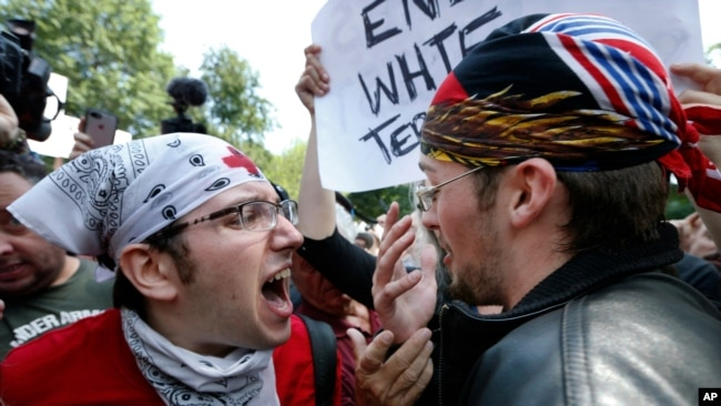 A counterprotester, left, confronts a supporter of President Donald Trump, Aug. 19, 2017, in Boston.
