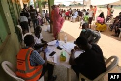 FILE - Health workers attend to people during a community COVID-19 coronavirus testing campaign in Abuja, Nigeria, on April 15, 2020.