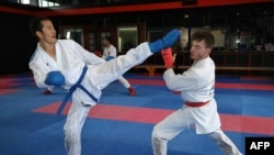 This picture taken on May 11, 2021 shows Afghan-born refugee and karate competitor Asif Sultani (L) training on the outskirts of Sydney as he competes for a place on the Refugee Olympic Team at the…