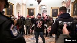 特朗普支持者道格拉斯·奧斯滕·詹森穿著支持匿名者Q的上衣,在國會大廈內與警察對峙。(2021年1月6日)