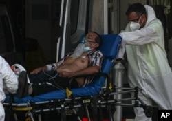26일 칠레 산티아고의 산호세 병원에서 의료진이 신종 코로나바이러스 감염증(COVID-19) 환자를 병원 건물로 옮기고 있다.