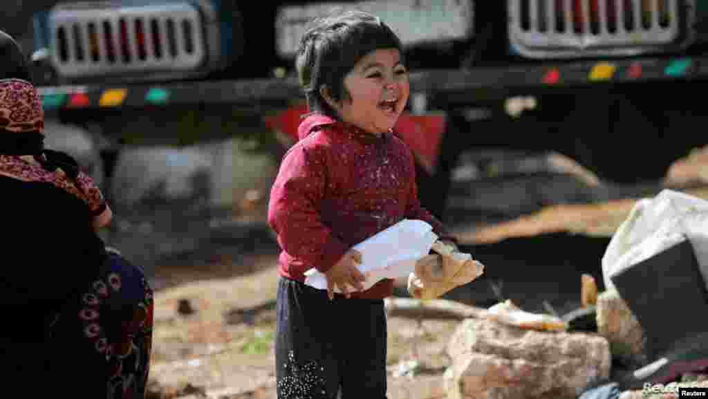 시리아 북서부 이들리브주 아자즈의 난민캠프에서 어린 아이가 빵을 들고 함박 웃음을 짓고 있다.