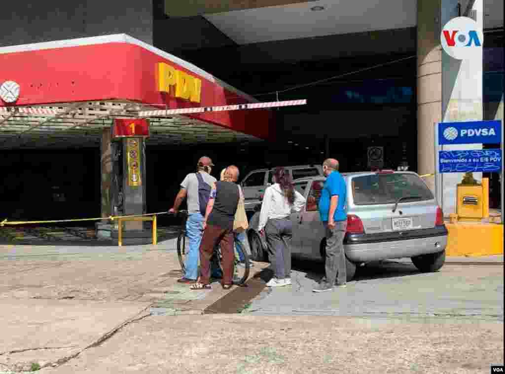 Personas se reunían mientras esperaban su turno para surtir en una de estación de servicio en el este de la capital venezolana, identificada como una de las 200 de empresarios privados que pueden vender a precio internacional y ser pagada en divisas.