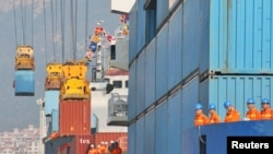 Workers look at cranes lifting containers onto cargo vessels at a port in Yantai, Shandong province, China, Oct. 17, 2019.
