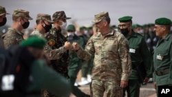 Gen. Stephen J. Townsend, head of the United States Africa Command, center, arrives alongside General Belkhir el-Farouk, Right, Moroccan Southern Zone Commander, to his right, to watch a large scale drill as part of the African Lion military…