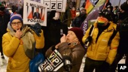 """Protesters with signs reading """"Free Media"""" gathered before Poland's state TVP building in Warsaw, Poland, on Wednesday, Feb. 10, 2021."""