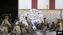 Turkish soldiers and Turkish-backed Syrian rebels gather near the Syrian border town of Ras al-Ayn, Oct. 12, 2019, as Turkey and its allies continued their assault on Kurdish-held border towns in northeastern Syria.