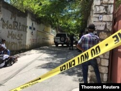 FILE - Journalists stand next to a yellow police cordon near the residence of Haiti's President Jovenel Moise after he was shot dead by unidentified attackers, in Port-au-Prince, July 7, 2021.