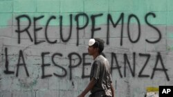 """FILE - A man with a misplaced face mask walks past graffiti on a wall that reads in Spanish """"Let's get hope back,"""" in Caracas, Venezuela, March 29, 2020."""