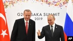Presiden Rusia Vladimir Putin (kanan) dan Presiden Turki Recep Tayyip Erdogan saat bertemu di sela KTT G20 di Osaka, Jepang, 29 Juni 2019.