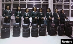 FILE - Ethiopian Airlines cabin crew members wait to get onboard the plane before takeoff at Bole international airport in the capital Addis Ababa, Nov. 18, 2015.