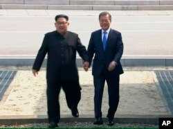 FILE - In this image taken from video provided by Korea Broadcasting System, April 27, 2018, North Korean leader Kim Jong Un crosses the border into South Korea, along with South Korean President Moon Jae-in for their historic face-to-face talks.