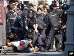 FILE - Police officers detain protesters during an unsanctioned rally in the center of Moscow, Russia, July 27, 2019.