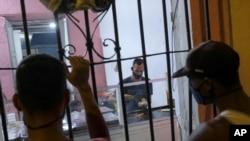 """Un hombre hace """"arepas"""" con el carrito de comida La Flaca instalado en la vivienda de la propietaria, mientras clientes esperan al otro lado de las barras en el barrio de Santa Rosalía en Caracas, Venezuela. Agosto 23, 2020."""