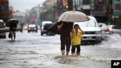 Warga setempat berjalan melewati banjir akibat hantaman badai tropis Kong-Rey di Tainan, Taiwan, Kamis (29/8).