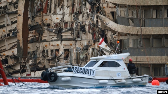 The damaged side of the capsized cruise liner Costa Concordia is seen at the end of the 'parbuckling' operation outside Giglio Harbor, Italy, Sept. 17, 2013.