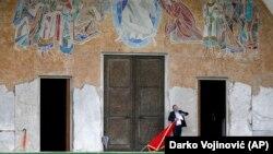 Čovek drži crnogorsku zastavu ispred Hrama Hristovog vaskrsenja u Podgorici, 15. oktobar 2016. (Foto: AP/Darko Vojinović)