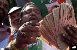FILE - An activist of Congress party holds banned 500 and 1000 rupee notes during a protest against the government's decision to withdraw high denomination notes from circulation, in front of Reserve Bank of India. in Hyderabad, Nov. 28, 2016.