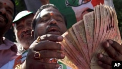 An activist of Congress party holds banned 500 and 1000 rupee notes during a protest against the government's decision to take high denomination notes from circulation, in front of Reserve Bank of India. in Hyderabad, Nov. 28, 2016.