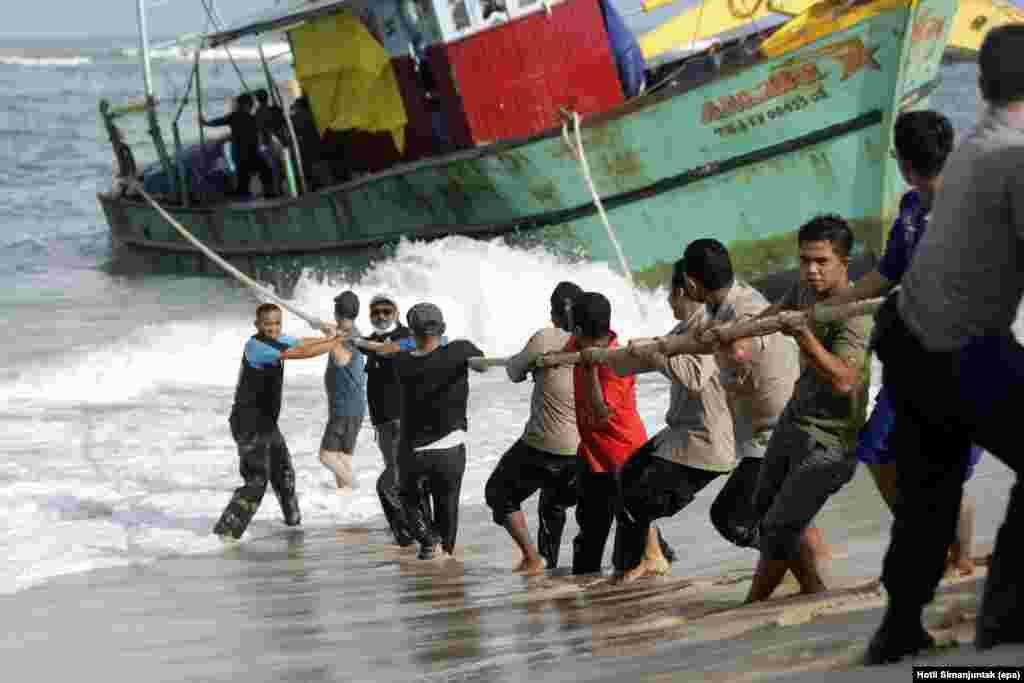 Polisi dan anggota TNI berusaha menarik kapal migran Sri Lanka, yang mengalami kerusakan mesin, di pantai Lhoknga, provinsi Aceh.