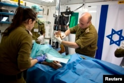 FILE - Members of the Israeli military medical team treat a Syrian man, who was injured in Syria's ongoing civil war, at a military hospital in the Israeli-occupied Golan Heights, close to the ceasefire line between Israel and Syria on Feb. 18, 2014.