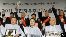Participants holding pictures of a Northern prison camp and N. Korean children in hunger shout slogans after they got their heads shaved during an anti-North Korea rally demanding a legislation of N. Korean human rights laws at a plaza in front of the Seo