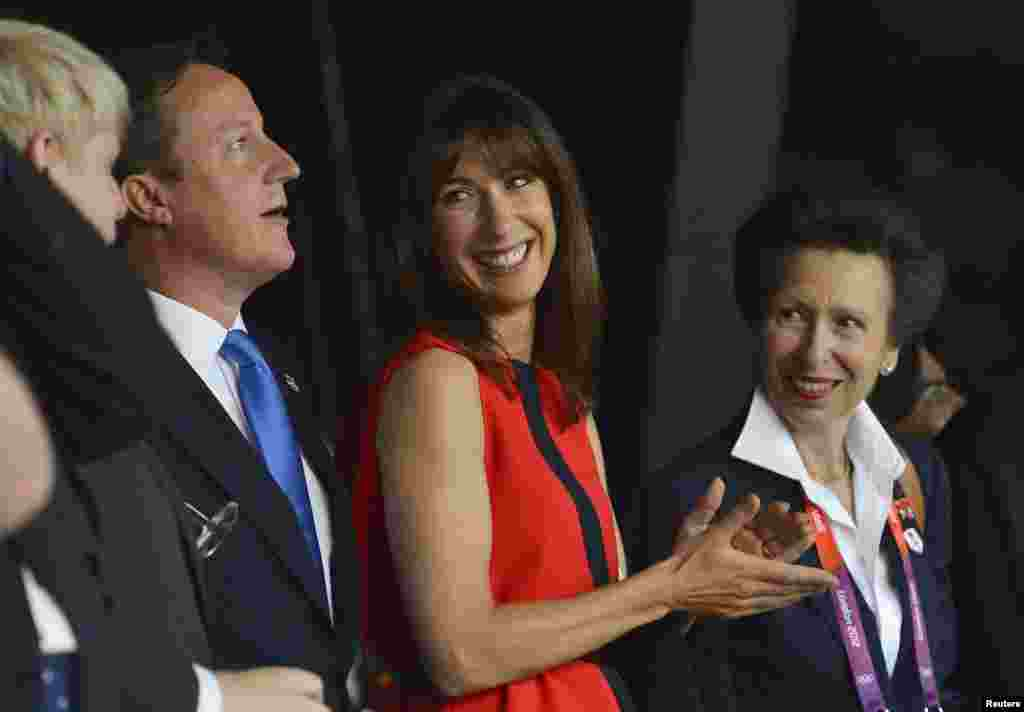 Britain's Prime Minister, David Cameron, (L) stands with his wife Samantha (C) and Princess Anne after arriving for the opening ceremony of the London 2012 Olympic Games at the Olympic Stadium July 27, 2012.