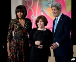 FILE - Then-First lady Michelle Obama, left, and Secretary of State John Kerry, right, honor Russian human rights activist, journalist Elena Milashina, with a Secretary of State's International Women of Courage Award during a ceremony at the State Department in Washington.