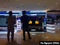 FILE - Shoppers check out smart TVs in Hanoi. Analysts recommend Vietnam retrain workers for the technology sector to meet the demand for new skills.