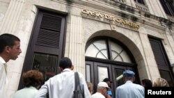 Cubanos esperan a cambiar pesos en moneda nacional (CUP) o dólares estadounidenses por CUC, hasta hace poco la única moneda libremente convertible en el que los ciudadanos podían hacer transacciones internas en el país.