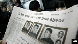 A South Korean newspaper shows photos of North Korean leader Kim Jong Il, center, his late father Kim Il Sung, left, and a photo South Korean media says of Kim's youngest son Kim Jong Un, At right bottom is Kim Jong-il's sister Kim Kyong Hui and top is he