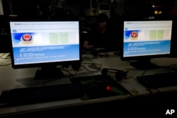 FILE - A computer user sits near displays with a message from the Chinese police on the proper use of the internet at an internet cafe in Beijing, China.