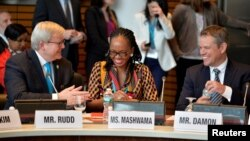 Actor Matt Damon, right, is welcomed to a meeting to promote his organization for universal clean water and sanitation, by former Australian Prime Minister Kevin Rudd, left, and Swaziland's Minister of Natural Resources and Energy Jabulile Mashwama, as part of the IMF and World Bank's 2017 Annual Spring Meetings, in Washington, April 20, 2017.
