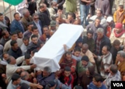 Warga di halaman pengadilan Benghazi, Sabtu (5/3) menggotong peti jenazah salah seorang korban ledakan gudang peluru sehari sebelumnya.