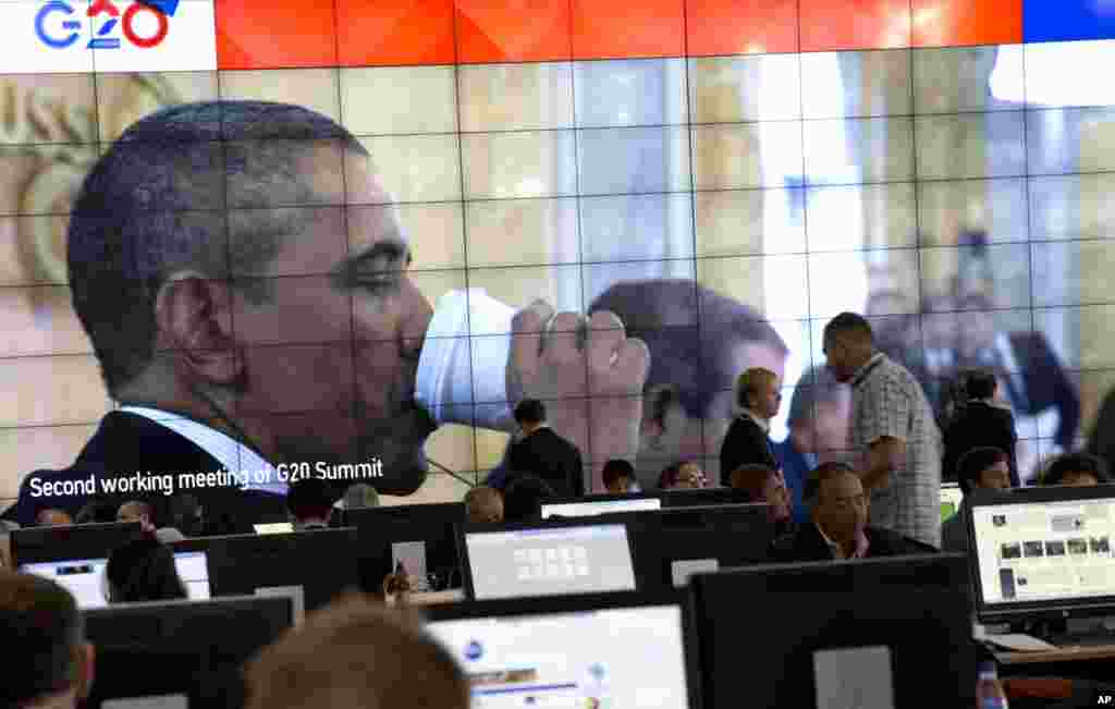 An image of U.S. President Barack Obama drinking out of a paper cup is shown on a large screen in the media center of a G-20 summit in St. Petersburg, Russia, Sept. 6, 2013.