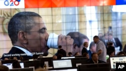 Presiden Obama minum dengan gelas kertas terlihat di layar lebar di media center KTT G-20 di St. Petersburg (6/9). Dalam KTT tersebut Obama mencari dukungan untuk menyetujui serangan terhadap Suriah atas penggunaan senjata kimia oleh rejim berkuasa di negara itu.