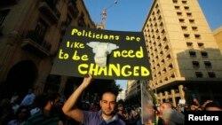 """Seorang demonstran di Beirut membawa poster bertuliskan """"Politisi seperti popok, harus diganti"""" pada sebuah protes Kamis (20/6). (Reuters/Sharif Karim)"""