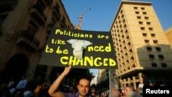 Một người biểu tình cầm biểu ngữ phản đối việc Quốc hội hoãn lại cuộc bầu cử, tại Beirut, 20/6/2013