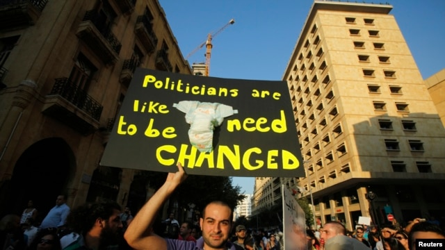 A protester holds up a placard during a rally against the extension of the current parliament's mandate, in Beirut, June 20, 2013.