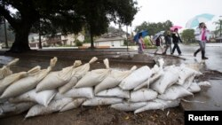 Residents walk past sandbags as rain begins to fall in Glendora, California, Dec. 2, 2014.