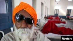 Seorang pria duduk di tempat tidur rumah sakit sambil menunggu perawatan medis pasca operasi katarak di Amritsar, India (5/12).