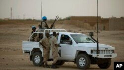FILE - United Nations peacekeepers stand guard at a polling station, during presidential elections in Kidal, Mali, July 28, 2013.