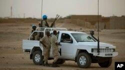 联合国维和部队士兵在2013年7月马里大选期间为一个投票站站岗。 (资料照片)