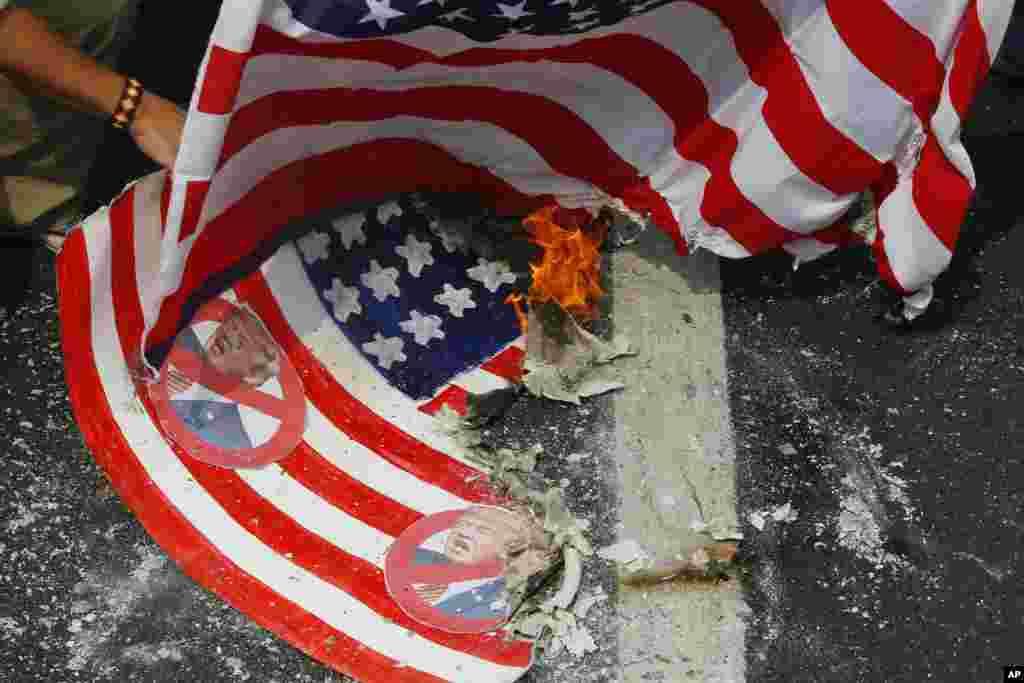 Les manifestants brûlent un faux drapeau des États-Unis et un vrai lors d'un rassemblement à l'ambassade des États-Unis pour coïncider avec l'investiture du président élu Donald Trump en tant que 45e président des États-Unis, le 20 janvier 2017.