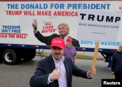 Bob Bolus, a supporter of U.S. Republican presidential candidate Donald Trump, gives the thumbs up to drivers as they pass by in Middleburg Heights, Ohio, March 15, 2016.