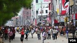 Pekerja garmen Bangladesh melemparkan berbagai benda ke arah petugas keamanan. Sekitar 15.000 pekerja memblokir berbagai jalan utama di Dhaka, sebagai bagian dari aksi protes atas upah rendah dan kondisi kerja yang memprihatinkan.