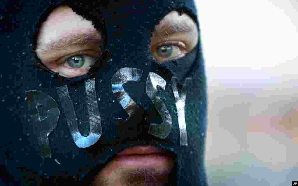 Um homem mascarado participa de uma manifestação em prol da banda russa em Sydney